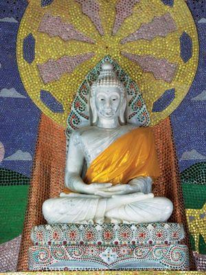 pada dinding di belakang Patung Buddha, juga didandani dengan ribuan tutup botol bekas.