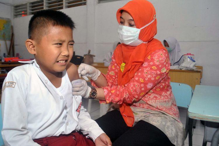 Petugas Puskesmas Sindangbarang Bogor memberikan imunisasi campak Measles Rubella kepada siswa di SD Insan Kamil, Kota Bogor, Jawa Barat, Rabu (9/8/2017). Pemberian imunisasi campak Rubella dilaksanakan dalam dua fase, yakni Agustus - September 2017 di seluruh wilayah Pulau Jawa dan pada Agustus - September 2018 di seluruh provinsi di luar pulau Jawa dengan target mencapai cakupan minimal 95 persen agar eliminasi campak dan pengendalian Rubella dapat terwujud pada 2020. ANTARA FOTO/Arif Firmansyah/ama/17