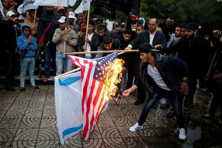 Warga Palestina membakar bendera Israel dan Amerika Serikat dalam sebuah demonstrasi terhadap niat Amerika Serikat memindahkan kedubes mereka ke Yerusalem dan mengenali Yerusalem sebagai ibukota Israel, di Kota Gaza, Rabu (6/12/2017).