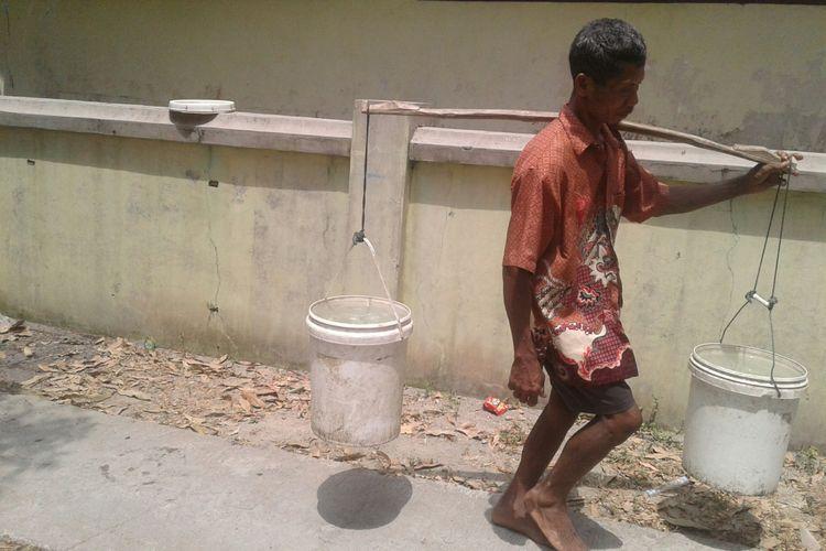 Seorang warga Dusun Kowang, Desa Ngargotirto, Kecamatan Sumberlawang, Kabupaten Sragen, Jawa Tengah memikul ember berisi air bersih, Jumat (31/8/2018).
