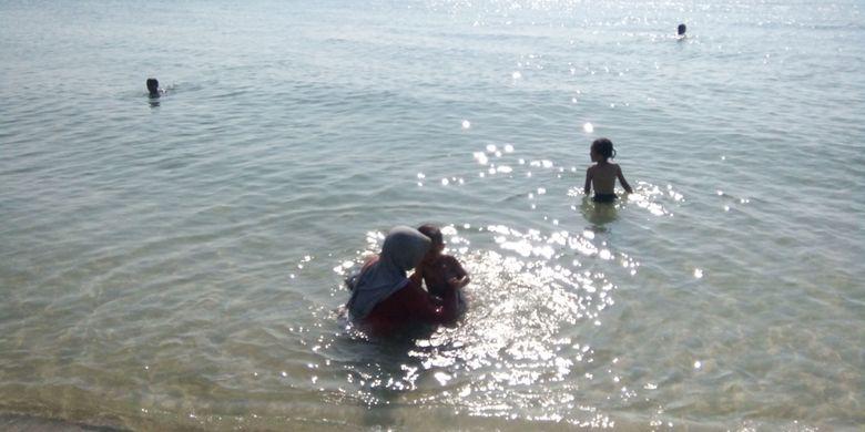 Pengunjung bermain air di Pantai Bondo,  Jepara,  Jawa Tengah, Sabtu (5/5/2018).
