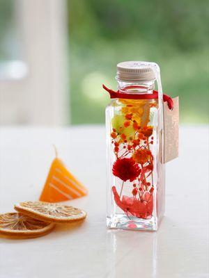 """""""Herbarium, Smile Mix"""", bunga berwarna merah yang menciptakan efek positif ke suasana hati. Bunga ini dimasukkan ke dalam botol berbentuk kotak segi empat"""
