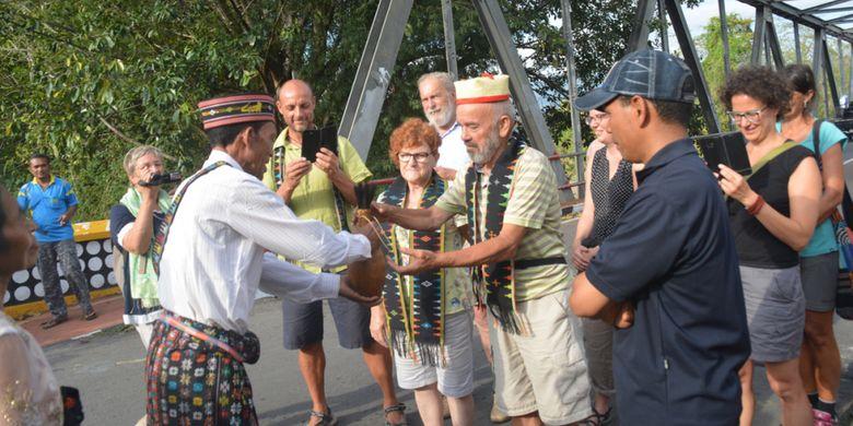 Ketua rombongan turis Italia dan Jerman menerima Moke Kepok Sundung di Jembatan Waemokel, Manggarai Timur, NTT, Rabu (15/8/2018).