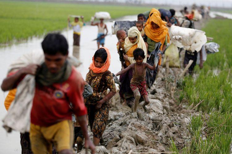 Pengungsi Rohingya berjalan di jalan berlumpur setelah menyebrangi perbatasan Bangladesh-Myanmar di Teknaf, Bangladesh, Minggu (3/9/2017).