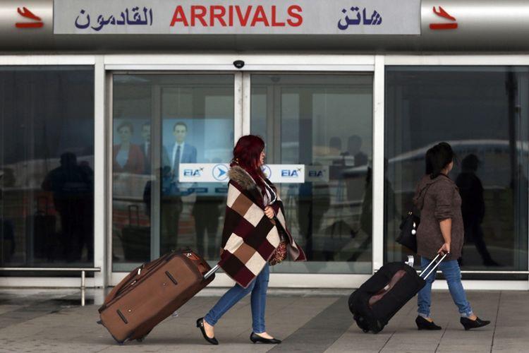 Calon penumpang melintas di luar bandara internasional Erbil di Kurdistan Irak. Pemerintah pusat Irak telah mencabut blokade udara di wilayah tersebut.