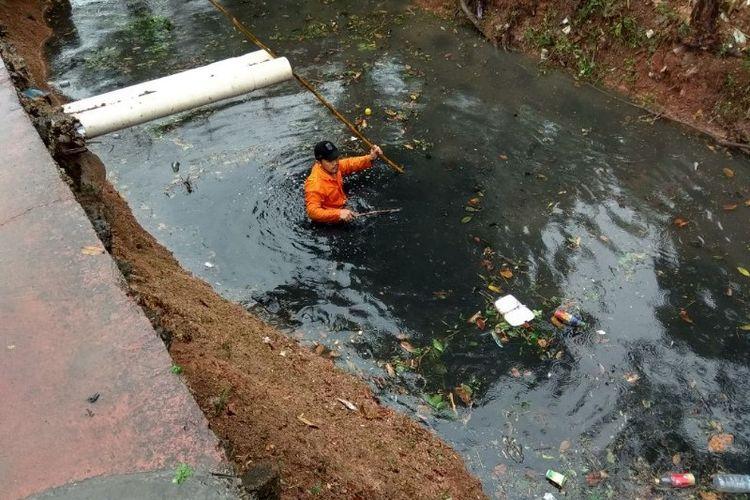 Petugas Pasukan Biru dari Dinas Tata Air membersihkan saluran air di Malaka Sari, Duren Sawit, Jakarta Timur pada Senin (25/6/2018).