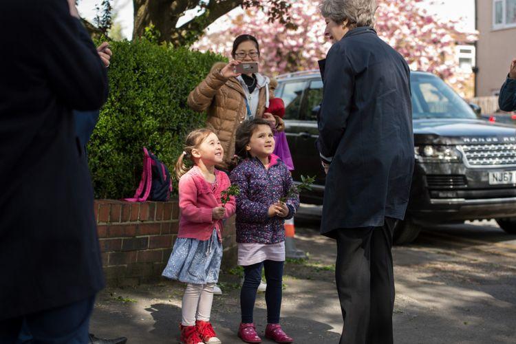Perdana Menteri Inggris Theresa May (tengah) berbicara dengan warga saat ia pergi setelah mengunjungi Sekolah Dasar Brooklands di Sale, dekat Manchester, Inggris bagian utara, 30 April 2018, sebagai bagian dari kampanye pemilihan lokal Partai Konservatif.