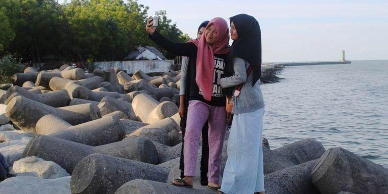 Pengunjung berswafoto di Pantai Bangka Jaya, Kecamatan Dewantara, Kabupaten Aceh Utara, Aceh, Senin (13/5/2019).