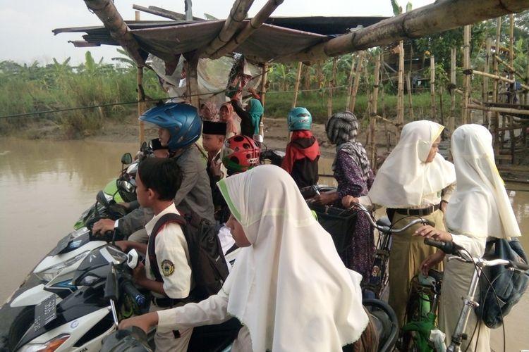 Pelajar dan karyawan memanfaatkan jasa penyeberangan Sungai Tuntang, Rabu (7/3/2018).