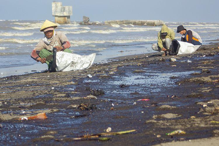 Warga mengumpulkan tumpahan minyak (Oil Spill) yang tercecer di Pesisir Pantai Cemarajaya, Karawang, Jawa Barat, Senin (22/7/2019). Tumpahan minyak tersebut tercecer di sepanjang pantai Sedari hingga pantai Cemarajaya akibat kebocoran pipa proyek eksplorasi minyak milik Pertamina.