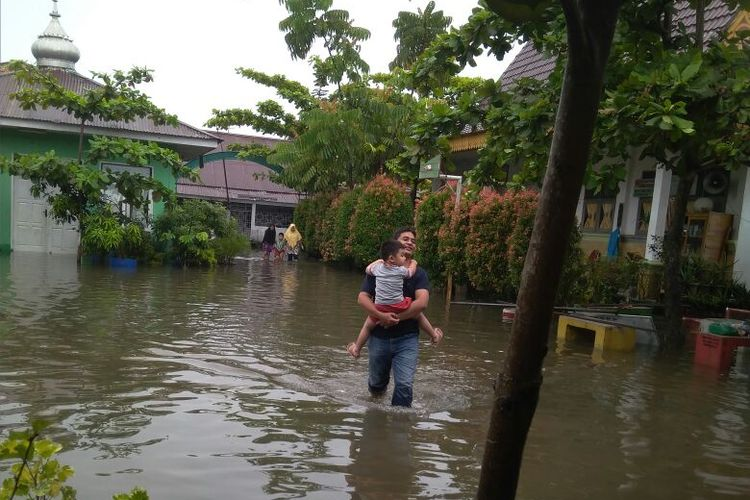 Warga mengarungi banjir untuk mencoblos ke TPS 034 di Jalan Fajar, Kecamatan Payung Sekaki, Pekanbaru, Riau, Rabu (27/6/2018)