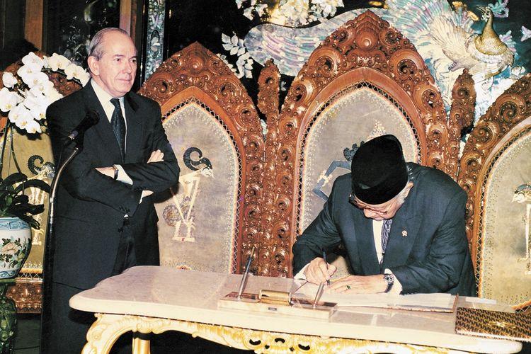 Direktur Pelaksana Dana Moneter Internasional (IMF) Michel Camdessusmenyaksikan Preisden Soeharto menandatangani nota kesepakatan bantuan di Jalan Cendana, Jakarta, pada 15 Januari 1998.