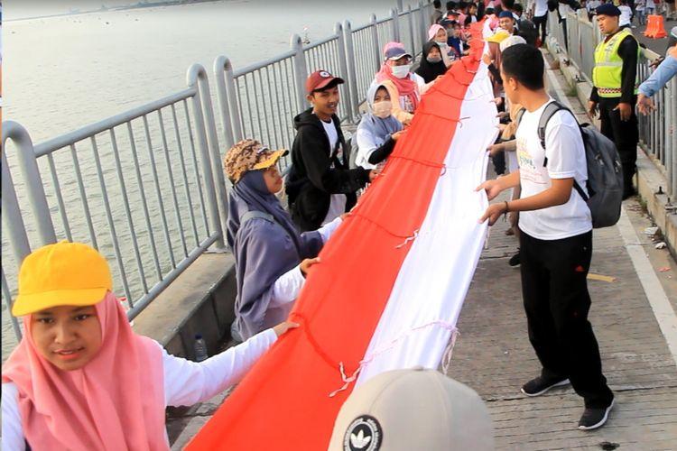 Bendera merah putih sepanjang 5,4 kilometer dibentangkan saat kampanye keselamatan berkendara di Jembatan Suramadu, Minggu (17/3/2019)
