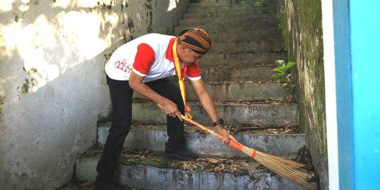 Gubernur Jawa Tengah, Ganjar Pranowo sedang membersihkan tangga di halaman Keraton Surakarta Hadiningrat, Jumat (29/3/2019) pagi.