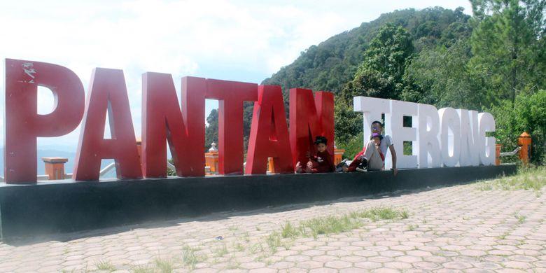 Wisatawan berfoto dengan latar tulisan Pantan Terong, di Desa Ulu Nuih, Kecamatan Bebesen, Kabupaten Aceh Tengah, Aceh.