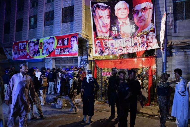 Petugas keamanan Pakistan berkumpul di lokasi bom bunuh diri di Peshawar pada Selasa (10/7/2018). (AFP/Abdul Majeed)