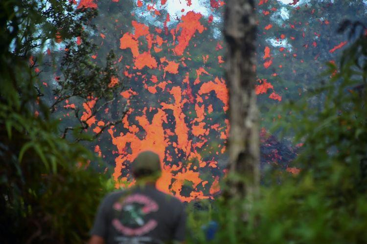 Seorang warga Hawaii melihat luapan lahar yang keluar dari celah tebing gunung Kilauea di Pulau Besar, Hawaii. Sekitar 10.000 warga telah diminta mengungsi untuk menghindari dampak letusan gunung berapi yang meletus pada Jumat (4/5/2018).