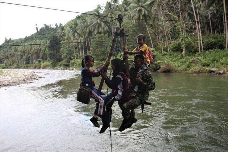 Sersan Kepala (Serka) Darwis dalam aksi heroiknya membantu para pelajar menyerberangi sungai di Desa Maroko, Kolaka, Sulawesi Tenggara.