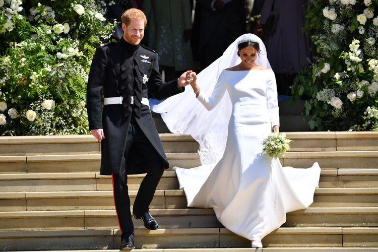 Pangeran Harry, Duke of Sussex dan istirnya Meghan, Duchess of Sussex saat keluar dari St Georges Chapel, Windsor Castle, 19 Mei 2018 setelah upacara pernikahan mereka. / AFP PHOTO / POOL AND AFP PHOTO / Ben STANSALL