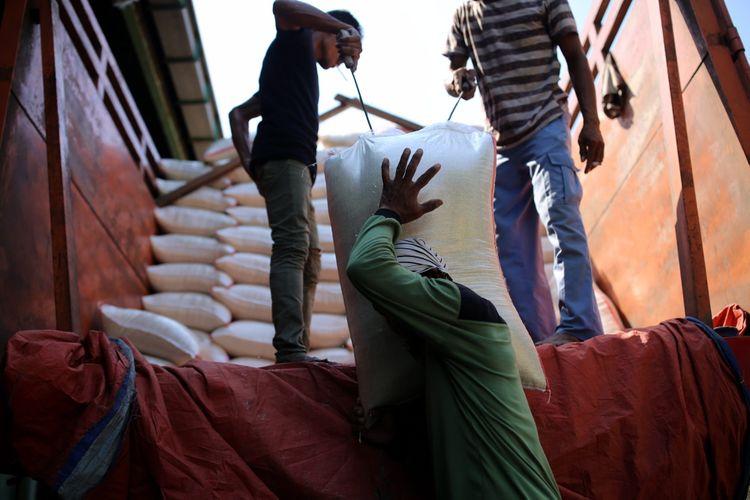 Buruh menurunkan beras Bulog di Pasar Induk Beras Cipinang, Jakarta Timur, Rabu (26/7/2017). Penetapan Harga Eceran Tertinggi (HET) untuk komoditas beras memberikan pengaruh yang besar kepada para petani dan pedagang sehingga menyebabkan pasokan beras ke pasar induk anjlok.