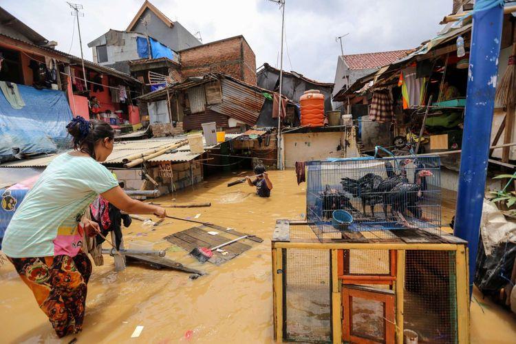 Warga beraktifitas saat banjir di Kampung Pulo, Jatinegara, Jakarta Timur, Selasa (6/2/2018). Banjir merendam ratusan rumah warga akibat luapan air dari Sungai Ciliwung.
