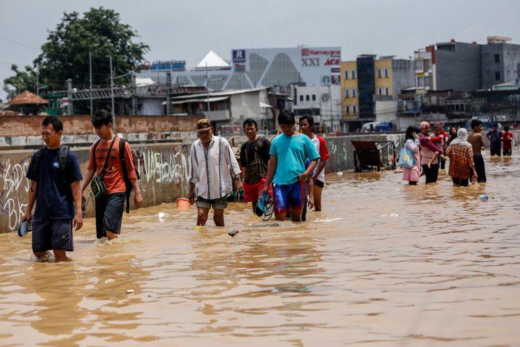 Warga berjalan melintasi banjir di Kampung Pulo, Jatinegara, Jakarta Timur, Selasa (6/2/2018). Banjir merendam ratusan rumah warga akibat luapan air dari Sungai Ciliwung.