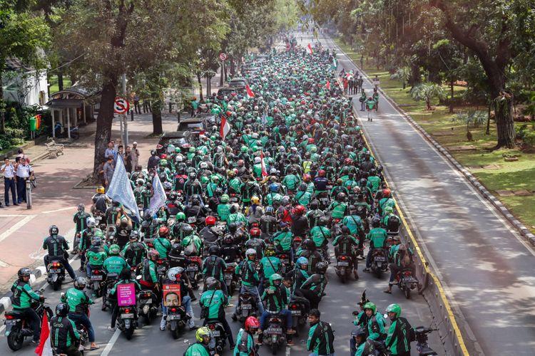 Pengemudi ojek online melakukan aksi unjuk rasa di depan Istana Negara, Jakarta Pusat, Selasa (27/3). Massa dari pengemudi ojek online menuntut pemerintah membantu untuk berdiskusi dengan perusahaan transportasi online agar merasionalkan tarif.