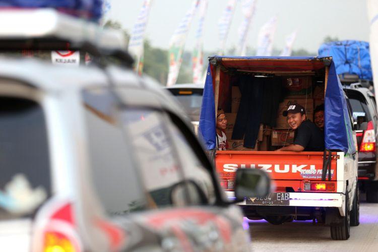 Sejumlah pemudik menaiki mobil bak terbuka saat memasuki rest area Tol  Pemalang-Batang, Jawa Tengah, Senin (11/6/2018). Jalan tol tersebut merupakan tol fungsional yang dibuka selama 24 jam hingga H+ 7 Lebaran.