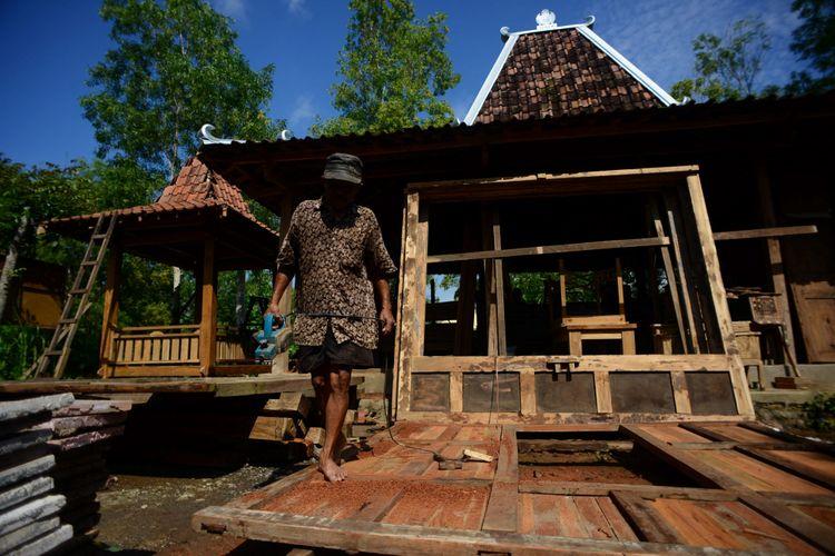 Pembuatan Rumah Joglo - Pekerja menggarap rumah joglo di PB Lestari, Dusun Krebet, Desa Sendangsari, Pajangan, Bantul, DI Yogyakarta, Jumat (23/1). Rumah tradisional Jawa tersebut dibuat berdasarkan pesanan dengan harga jual berkisar Rp 150 juta - Rp 250 juta per unit. Tempat usaha tersebut menjadi sumber  penghasilan bagi 50 pekerjanya.  Kompas/Ferganata Indra Riatmoko (DRA) 23-01-2015