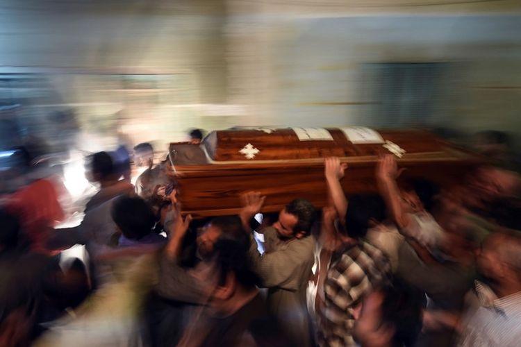 Kerabat umat Kristen Koptik yang tewas ditembaki ISIS pada Jumat (26/5/2017) mengangkat peti jenazah usai misa pemakaman di katedral Abu Garnous Cathedral di kota Maghagha, provinsi Minya, Mesir.