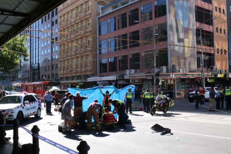 Petugas paramedis menangani para korban yang tertabrak di depan Stasiun Flinders Street. (ABC News/Gus Goswell)