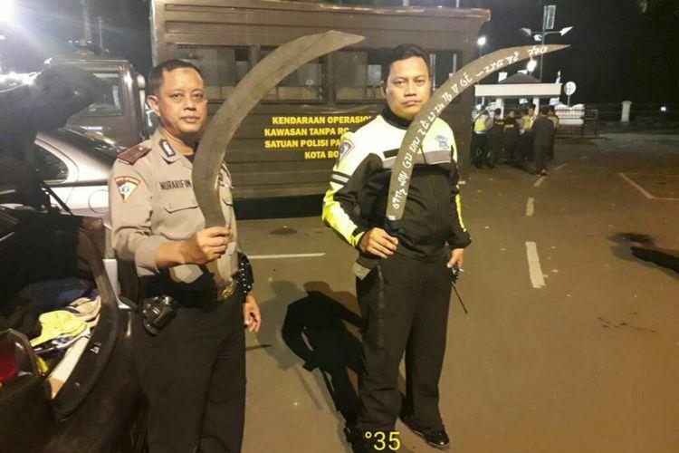 Petugas kepolisian mengamankan sejumlah senjata tajam yang digunakan untuk tawuran oleh sekelompok pemuda di Jalan Raya Pajajaran, Bogor, Senin (4/6/2018).