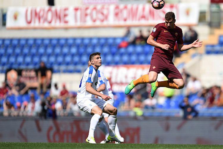 Striker AS Roma, Edin Dzeko, menyundul bola dengan dibayang-bayangi pemain Atalanta saat kedua tim bertemu pada pertandingan Serie A di Stadion Olimpico, Sabtu (15/4/2017).
