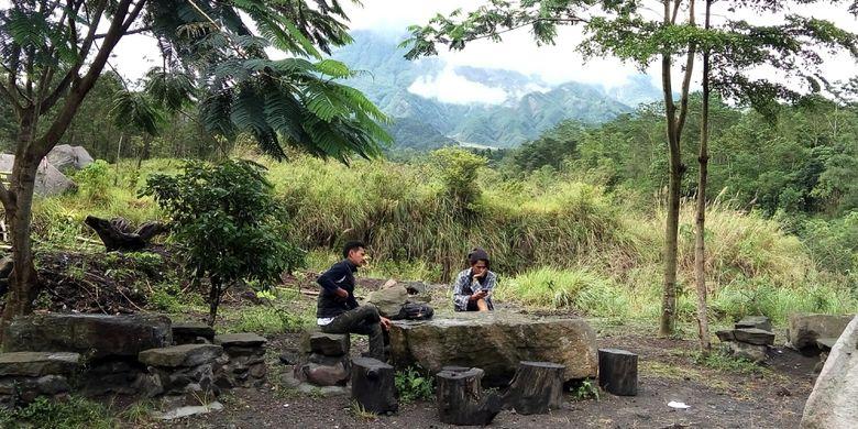 Dua pengunjung warung Kopi Merapi saat menunggu pesanan kopi sembari menikmati alam kaki Gunung Merapi.