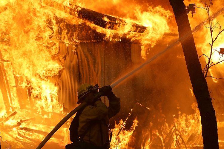 Seorang anggota pemadam kebakaran berusaha menjinakkan Api Camp yang melalap Magalia, California, Amerika Serikat pada Jumat (9/11/2018). Api Camp dan Api Woolsey menjalar dan menewaskan sembilan orang, serta 150.000 orang mengungsi.