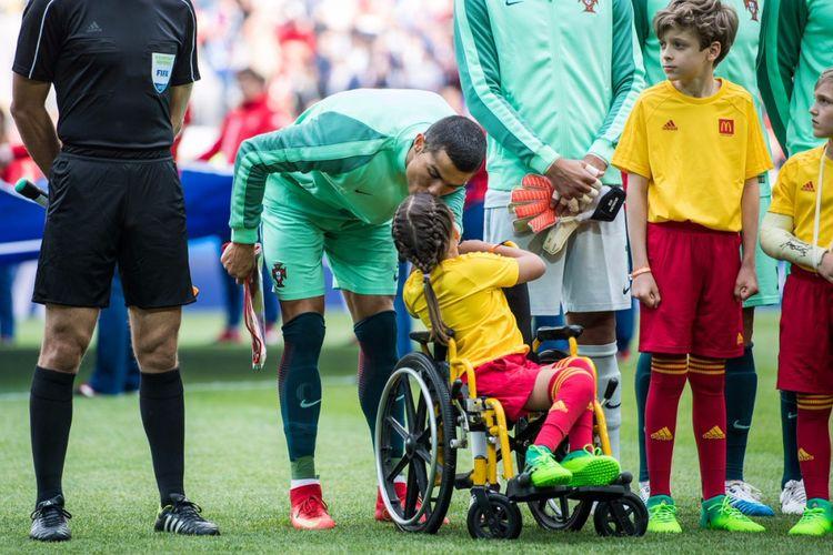 Jelang kick-off laga Rusia versus Portugal, Ronaldo kecup kening anak penyandang disabilitas, Polina Haeredinova.