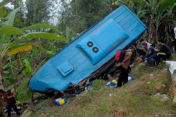 Sejumlah warga melihat sebuah bus berpenumpang wisatawan yang masuk jurang di Tanjakan Letter S, Cikidang, Sukabumi, Jawa Barat, Sabtu (8/9/2018). Data Polres Sukabumi menyebutkan kecelakaan lalu lintas tunggal ini mengakibatkan 21 orang tewas dan 17 luka-luka berat dan ringan.