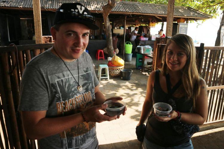 Dua wisatawan mancanegara asal Jerman akan melepaskan penyu dari tempat konservasinya di Pantai Segara Ayu, Sanur, Bali, Jumat (28/9/2018).