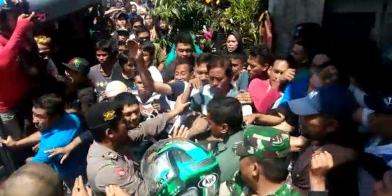 Ratusan warga Tanetea, Desa Bontosunggu, Kecamatan Bajeng, Kabupaten Gowa, Sulawesi Selatan berusaha menghakimi seorang pelaku jambret saat dievakuasi oleh petugas, Minggu, (13/1/2019).