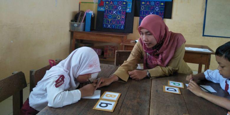Zuliawati Ninggsih, Guru SDN 004 Malinau Kota, Kabupaten Malinau membimbing anak yang lamban membaca dengan menggunakan kartu huruf. Penggunaan metode ini dinilai berhasil membantu anak lebih cepat membaca.