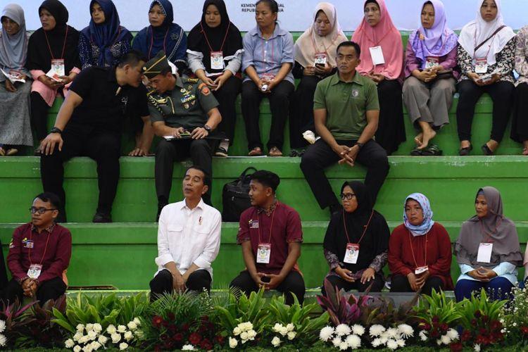 Presiden Joko Widodo tampak berbincang dengan salah satu penerima PKH yang duduk di sebelahnya di GOR Ciracas, Jakarta Timur, Kamis (10/1/2019).