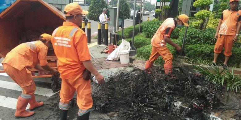 Pasukan oranye atau petugas PPSU Kelurahan Kuningan Barat menemukan gulungan kulit kabel, di gorong-gorong Jalan Gatot Subroto, Jakarta Selatan.