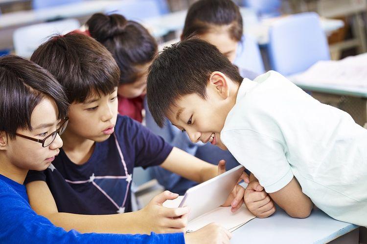Anak-anak sedang menggunakan gadget di kelas
