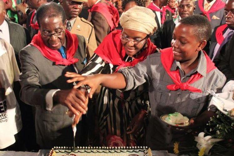 Chatunga Bellarmine Mugabe (kanan) bersama ayah dan ibunya saat merayakan ulang tahun Robert Mugabe ke-87 pada 2011.