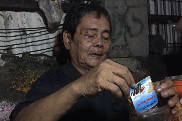 Pak Nasik menuangkan bubuk Kopi Liong.