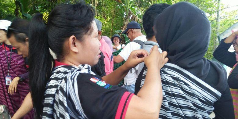 Wisatawan ke situs budaya Benteng Liya, Wakatobi, Sulawesi Tenggara harus mengenakan kain tenun adat setempat.
