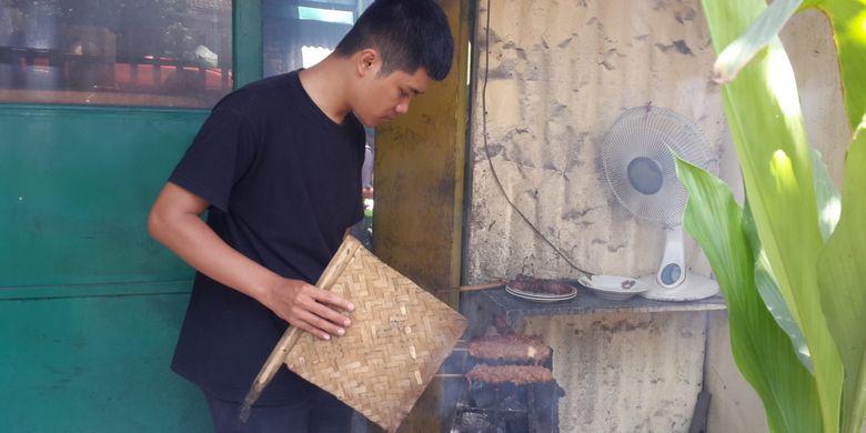 Achmad Kabir, pengelola Warung Sate Gebug di Kota Malang saat membuat sate gebug untuk pelanggannya, Minggu (20/1/2019).