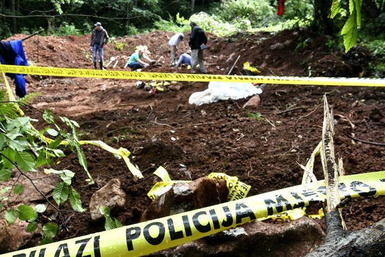 Anggota tim ahli forensik Bosnia dan sejumlah pekerja lain mencari jenazah manusia, di lokasi kuburan massal yang baru ditemukan di Desa Tugovo, dekat Kota Vlasenica, Bosnia timur, pada tanggal 13 September 2017.