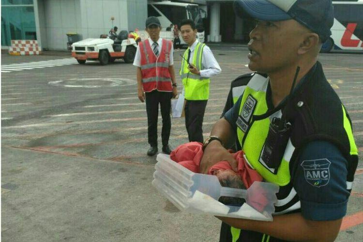 Petugas Bandara memberikan pertolongan pada bayi yang lahir dalam pesawat
