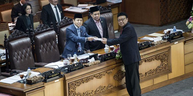 Menteri Dalam Negeri Tjahjo Kumolo (kanan) menyerahkan laporan pandangan pemerintah kepada Ketua DPR Setya Novanto (kiri) disaksikan Wakil Ketua DPR Fahri Hamzah (kedua kiri) saat rapat sidang Paripurna DPR ke-32 masa persidangan V tahun sidang 2016-2017 di Kompleks Parlemen Senayan, Jakarta, Jumat (21/7/2017) dini hari. DPR mengesahkan RUU Pemilu menjadi undang-undang setelah melalui mekanisme dan memilih opsi A, yaitu Presidential Threshold sebesar 20 persen kursi DPR atau 25 persen suara nasional.